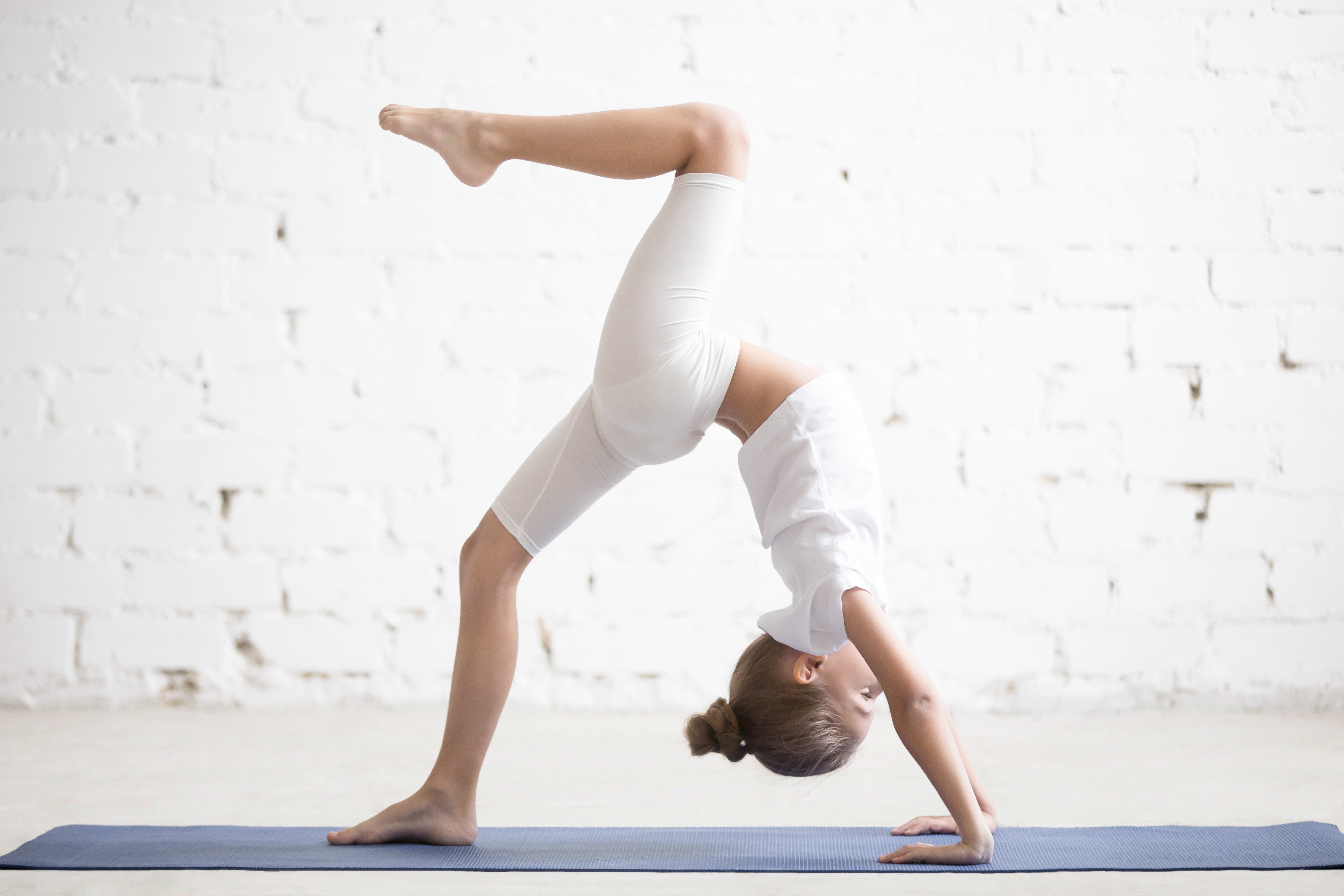 Girl child practicing yoga or fitness, standing in Bridge exercise, One legged Wheel pose, working out wearing sportswear, t-shirt, pants, indoor full length, white loft studio background
